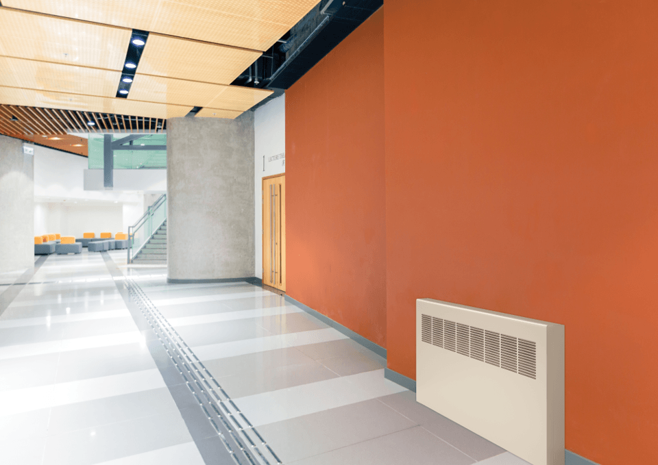 Front view of a convector unit installed in an orange hallway